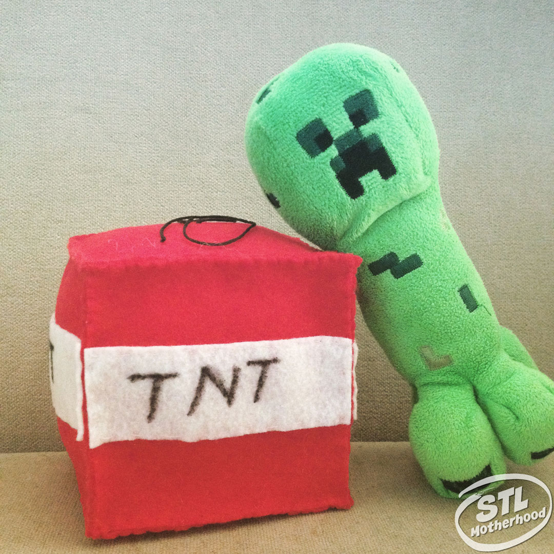 Toy creeper leaning on a handmade TNT plushy made of felt