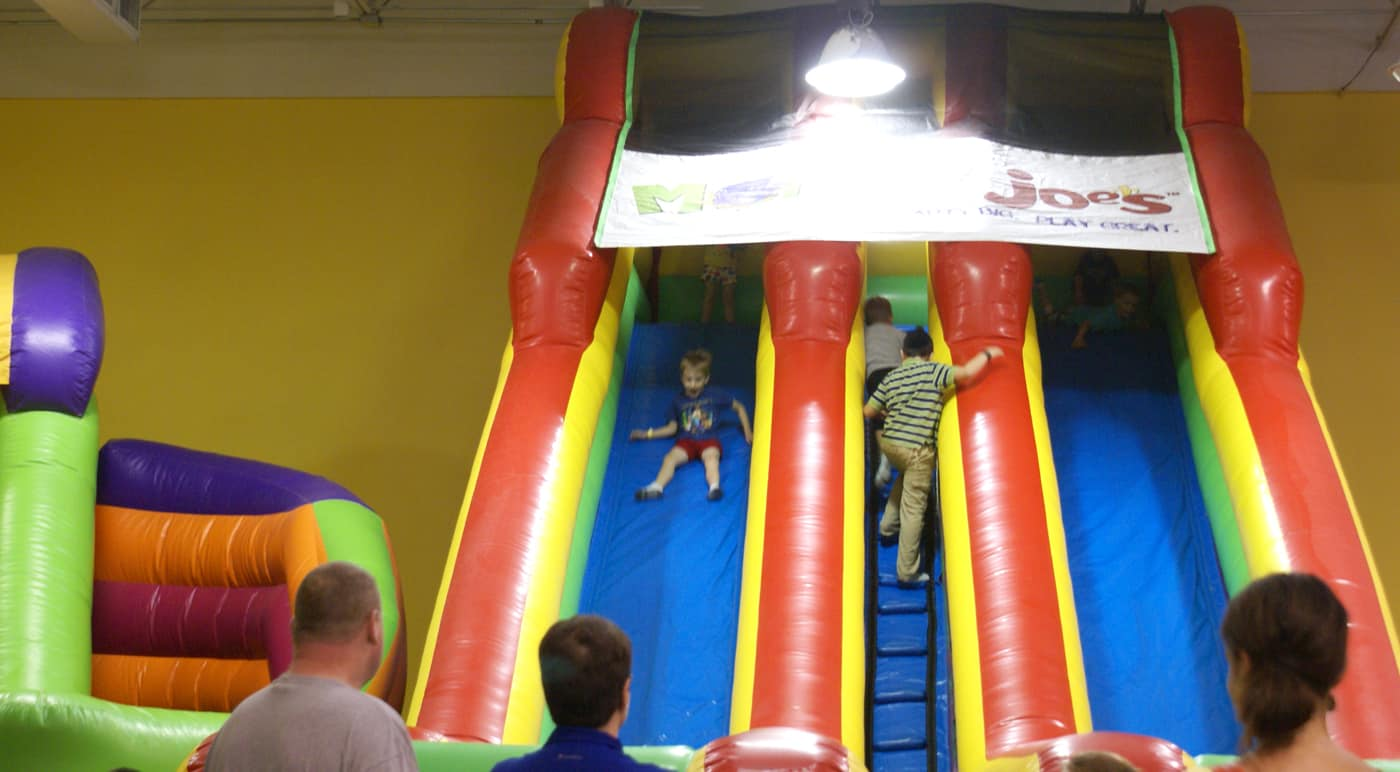 kid on a inflatable slide at Monkey Joe's indoor bounce house