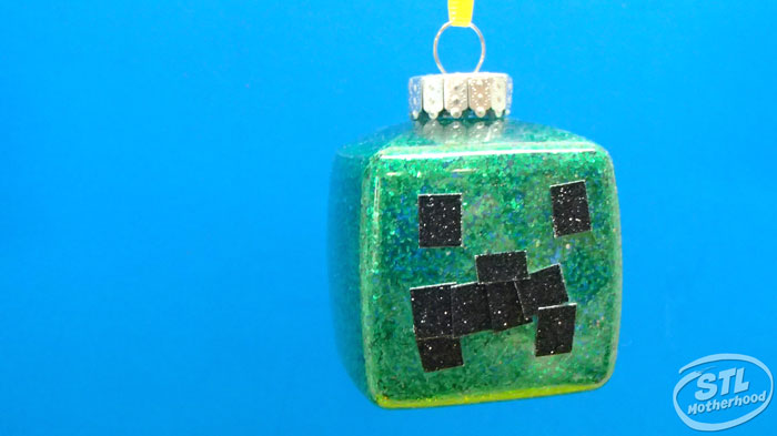 square Christmas ornament with green glitter and black glitter stickers to look like a Minecraft Creeper face