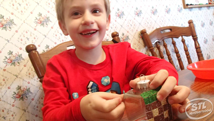 young boy in red shirt making a minecraft grass block Christmas ornament