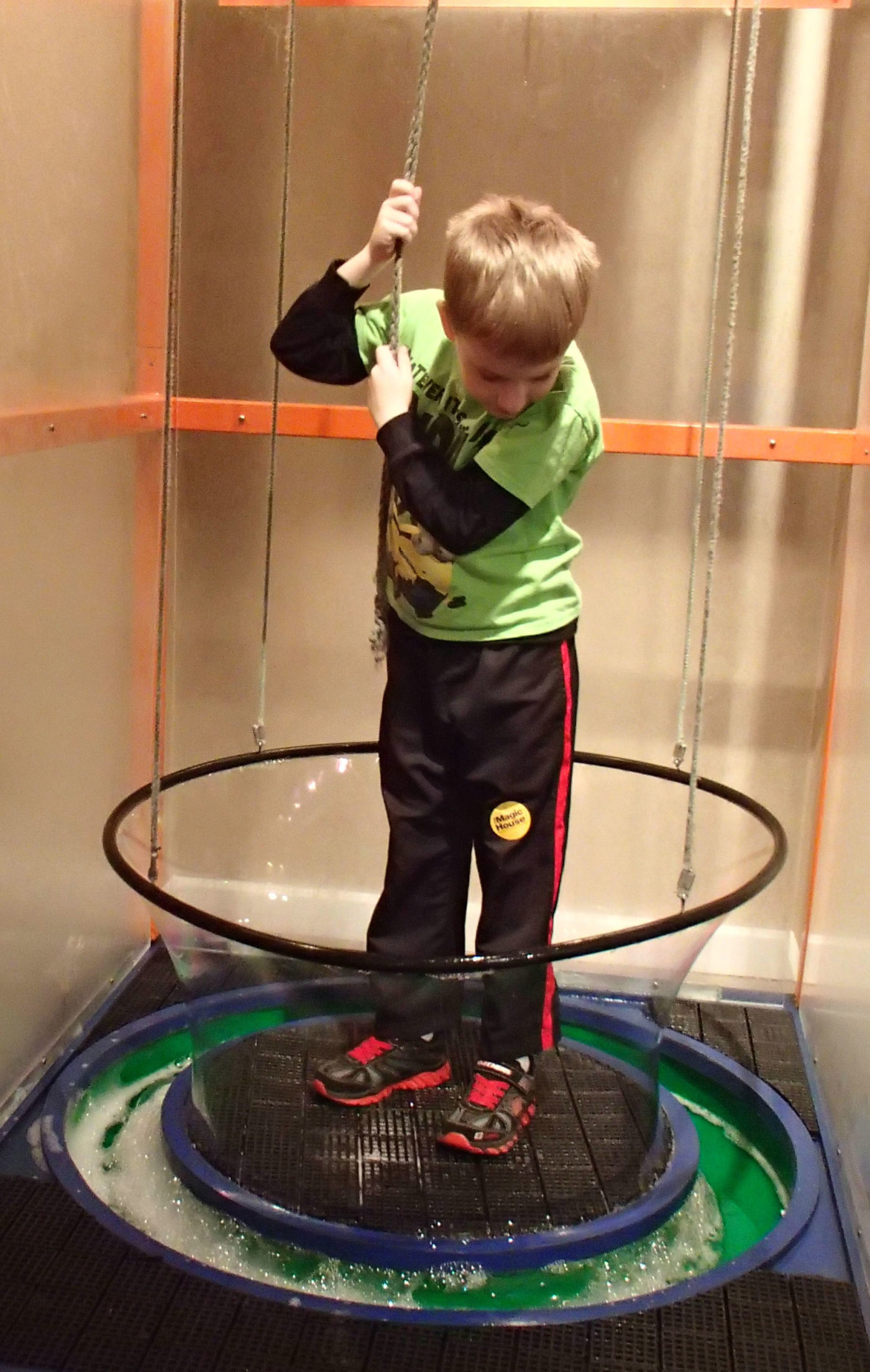 small child at the Magic House making a human sized bubble