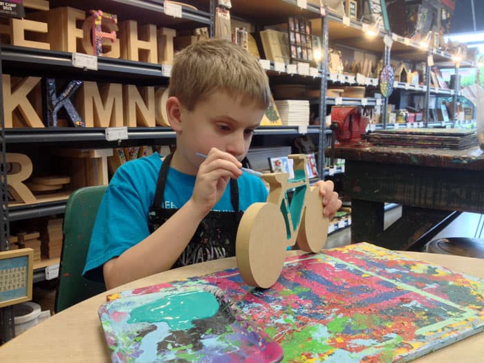 kid painting wooden bike at yucandu art studio