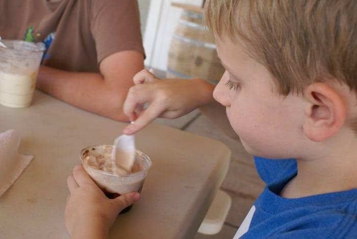 kid eats ice cream in a cup
