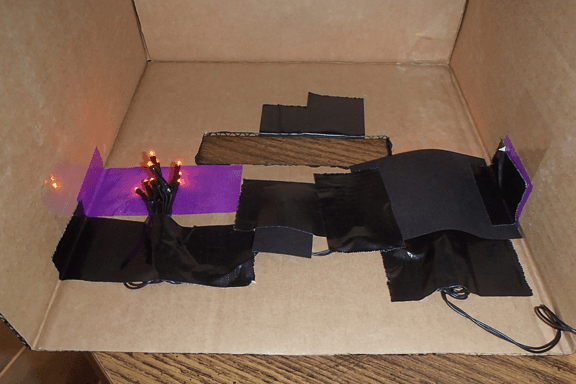 inside the Enderman costume head showing purple twinkle lights