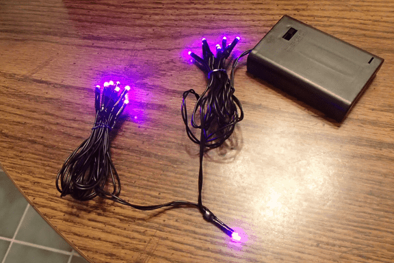 purple twinkle lights on a battery pack