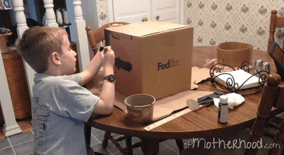 young boy at table making the enderman costume head from a box