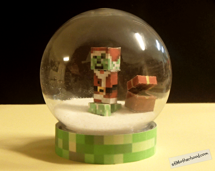 Minecraft creeper in Santa suit inside a dry snow globe with no water, and salt for snow.