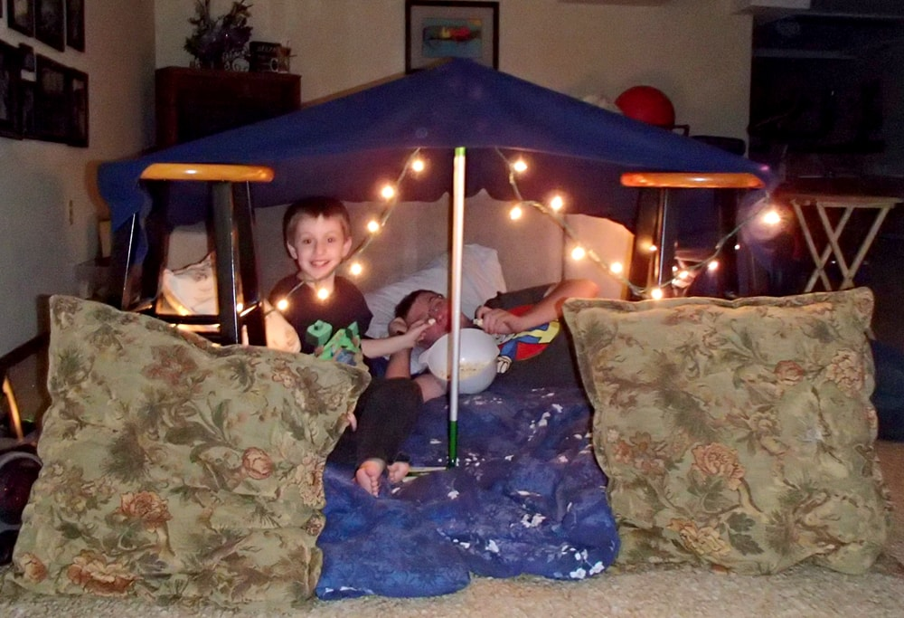 two kids in a fort made of blankets and pillows