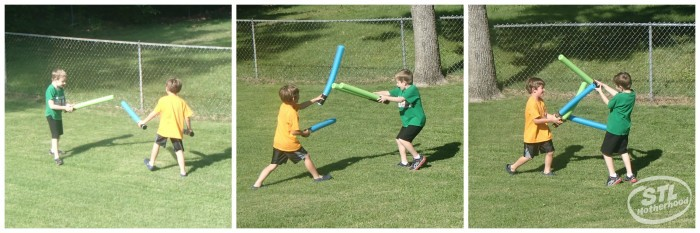 2 boys playing with Star Wars Light Sabers made from pool noodle on a green lawn