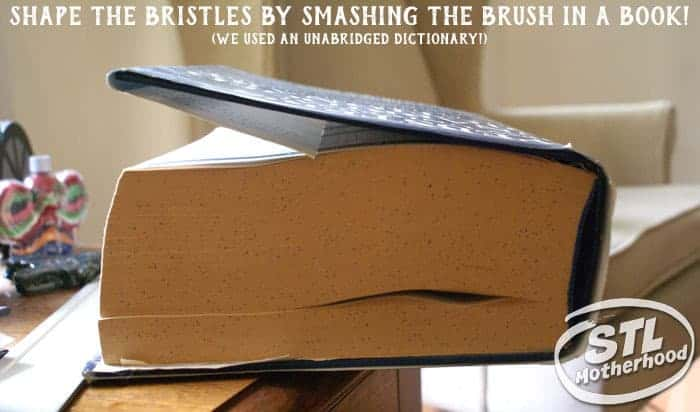 shaping the bristles of a brush bot by smashing it in a large book