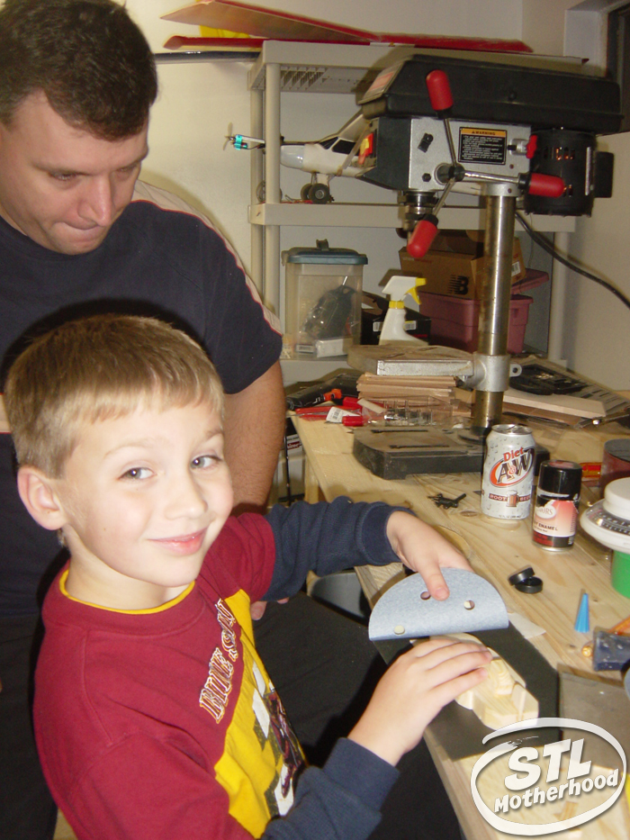 Boy and his dad in a home workshop making a pinewood derby car