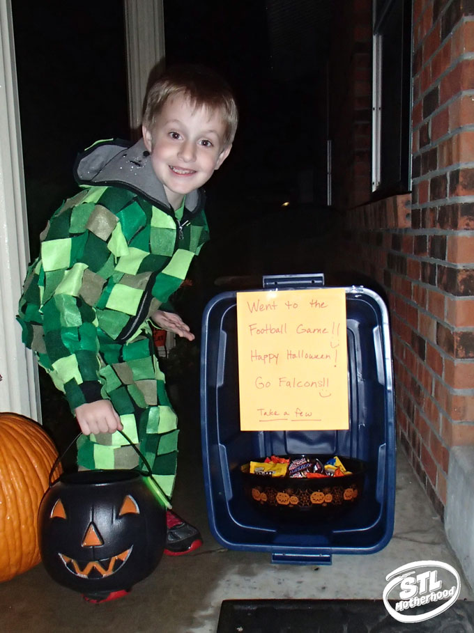 Kid trick or treating in a home made Minecraft Creeper costume