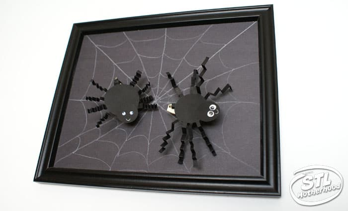 Halloween Brush Bot dressed as spiders on a picture frame with a web.