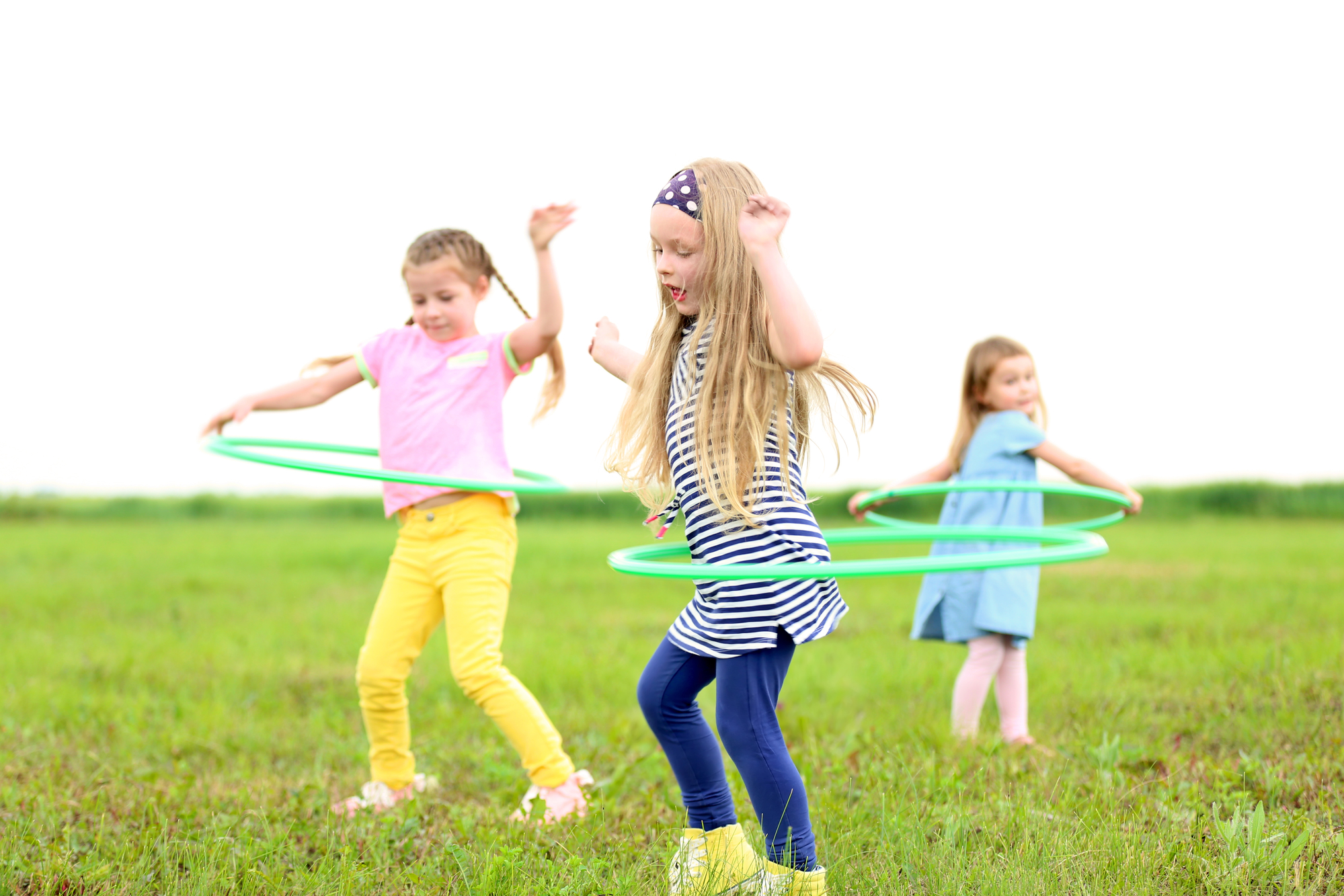 Children having fun with hula hoops outdoor