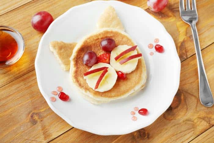 Plate with creative homemade pancake on wooden table
