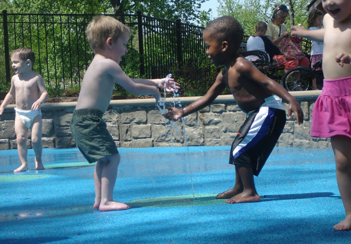 Two preschool boys in swim trunks--one white, one African American--make friends at a splash pad in the Children's Garden at the Missouri Botanical Garden.