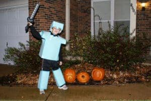 Child dressed in Minecraft costume for Halloween, foam armor plate, helmet and leggings. He is standing by jack-o-lanterns.
