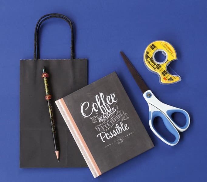 things needed to make a book cover for Halloween: gift bag, scissors, tape and journal to cover