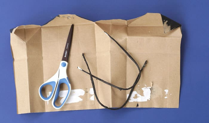 cutting up a gift bag to make a book cover with scissors