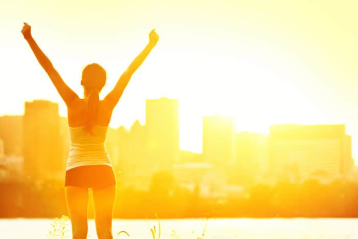 Success winner woman standing with arms up joyful after outdoors workout. Half silhouette on sunny warm summer day with city skyline in background,