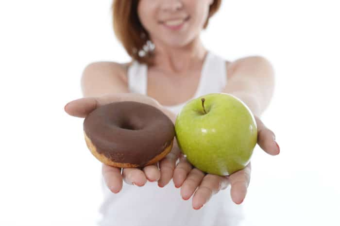 Young sport Woman with Apple and Chocolate Donut in Hands to choose