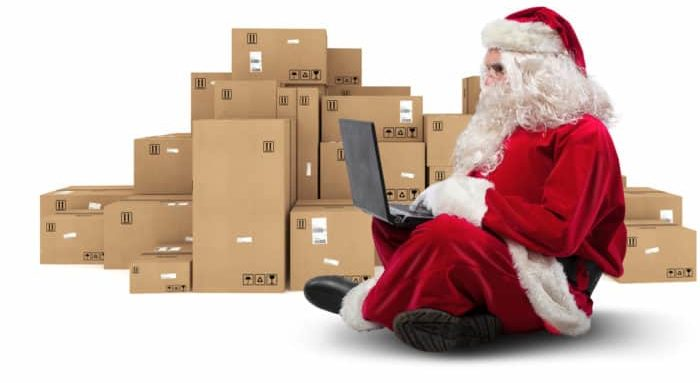 Santa Claus sitting with laptop and with Christmas boxes around