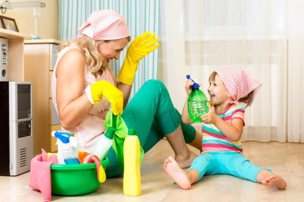 happy mother with kid cleaning room and having fun