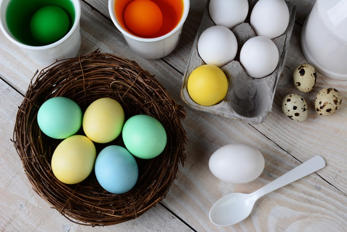 High angle view of Dying Easter Eggs. Dyed eggs in a nest with eggs in dye solution and other eggs ready to be dunked. Horizontal format on a rustic farmhouse style kitchen table.