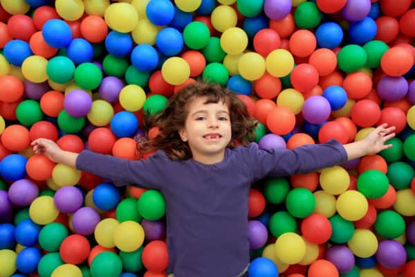 colorful balls funny park little girl lying gesturing happy