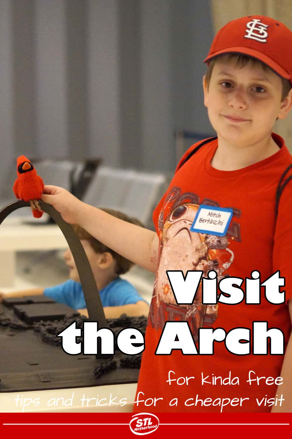 kid at Gateway Arch museum holding toy Cardinal bird on model of the Arch