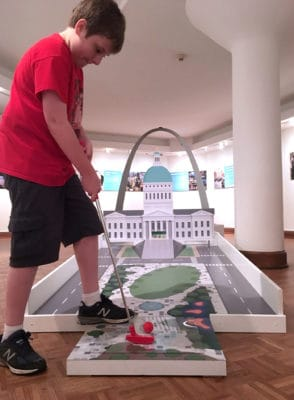 Kid plays mini golf at an art gallery. The hole is designed to look like the Gateway Arch grounds.