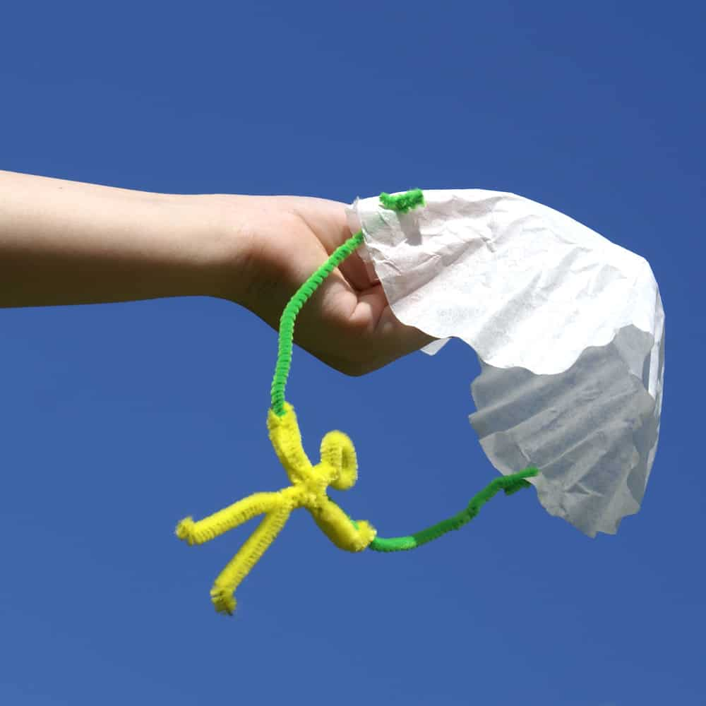 child's hand holding coffee filter parachute toy against a blue sky