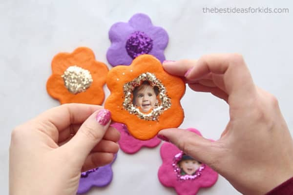 cookie cutter flowers made from salt dough and turned into magnets--painted, glittered and has a kid's picture in the middle