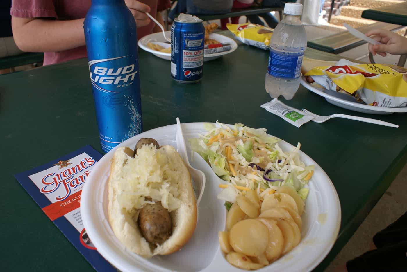 Lunch at Grant's Farm: brat on bun with sauerkraut, potato salad and green salad on paper plate with Bud Light.
