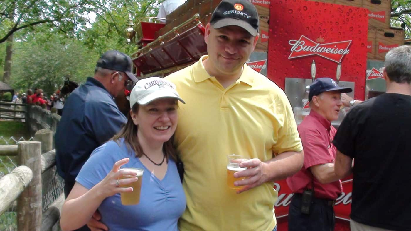 The blogger and her husband having a free beer from the Budweiser horse drawn wagon.
