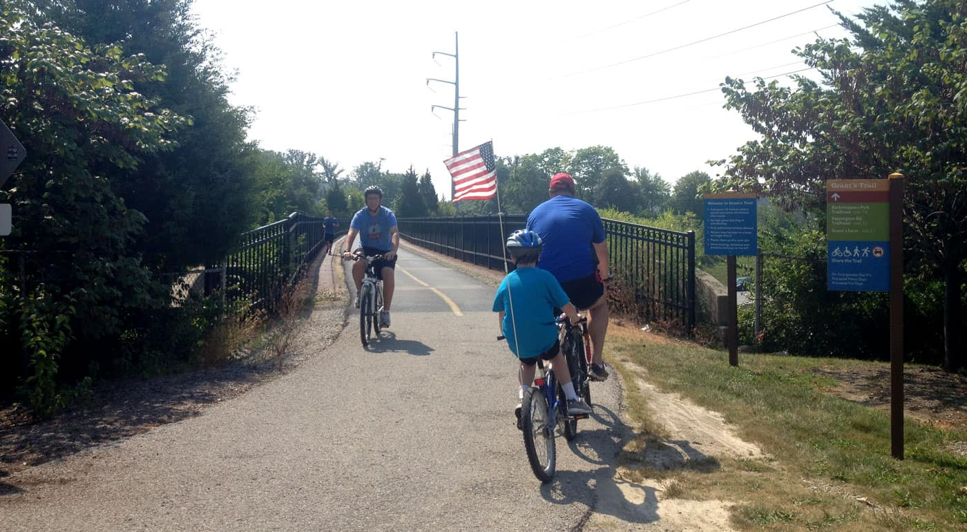 Dad and son on tagalong bike riding paved trail, with American flag on back of bike.