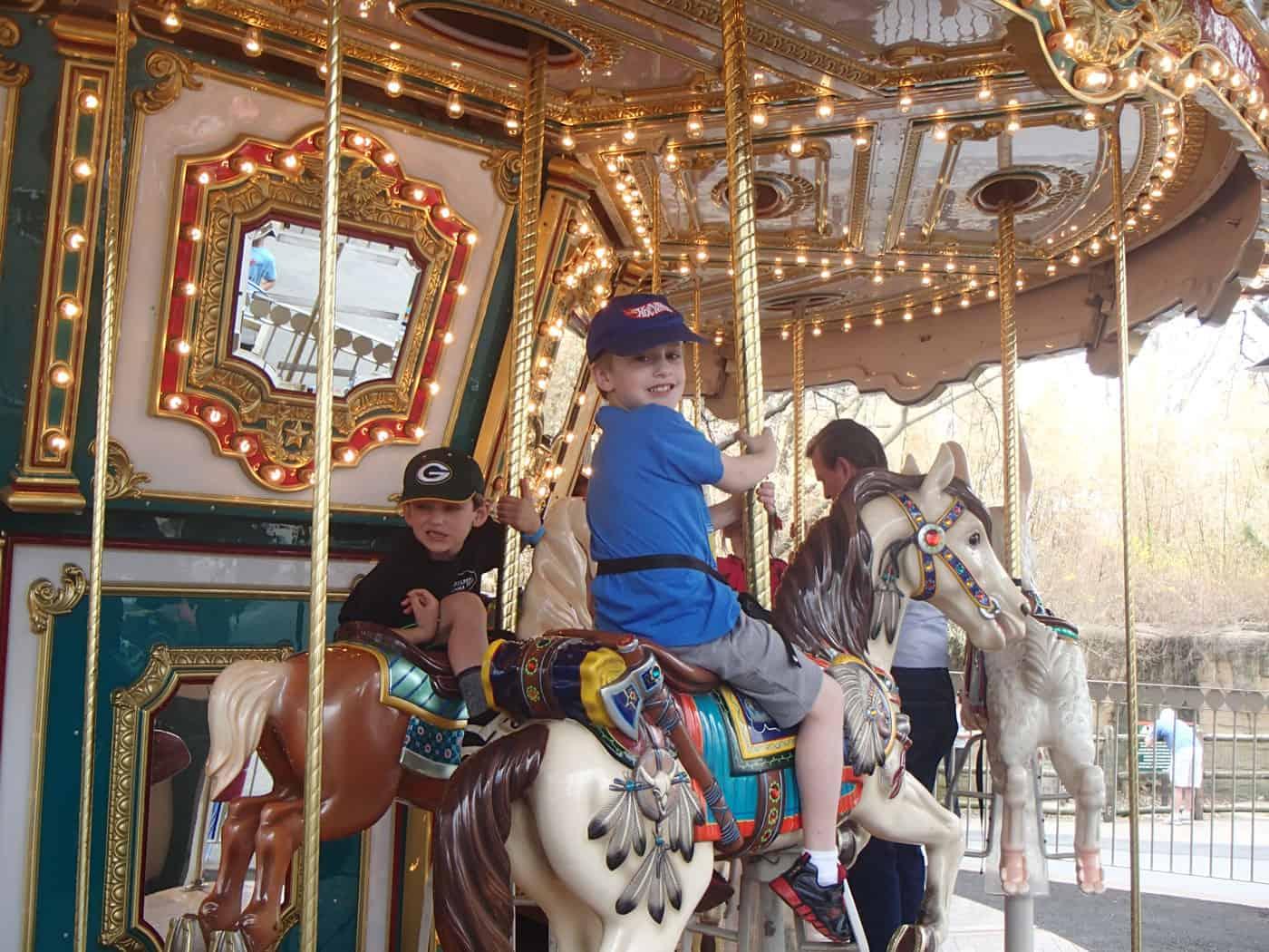 boys riding the carousel horses at Grant's Farm