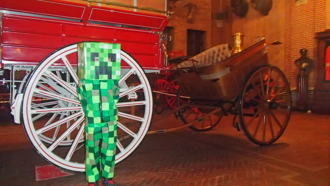 Kid in Minecraft Creeper costume stands next to large wagon wheel at Grant's Farm