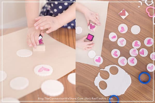 Child's hands using rubber stamp to make heart stamped clay magnets.