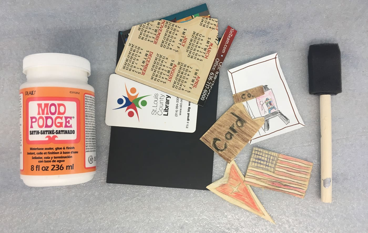 supplies for making decoupage art: mod podge, old sheet magnets, foam brush and kid drawings or doodles.