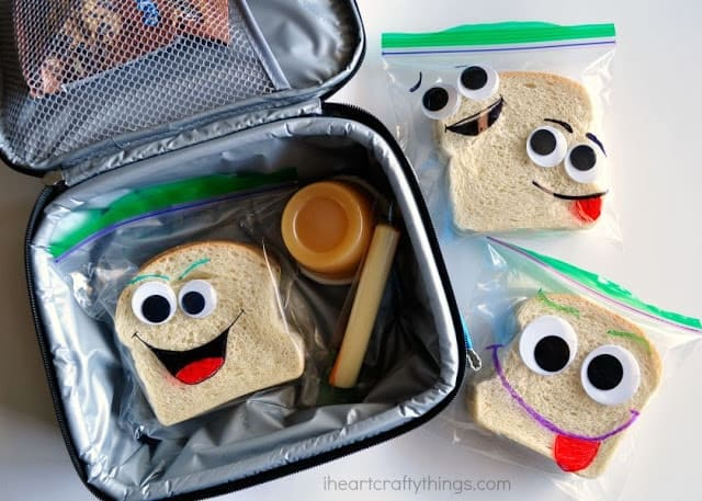 Lunch box holding sandwiches decorated with googly eyes