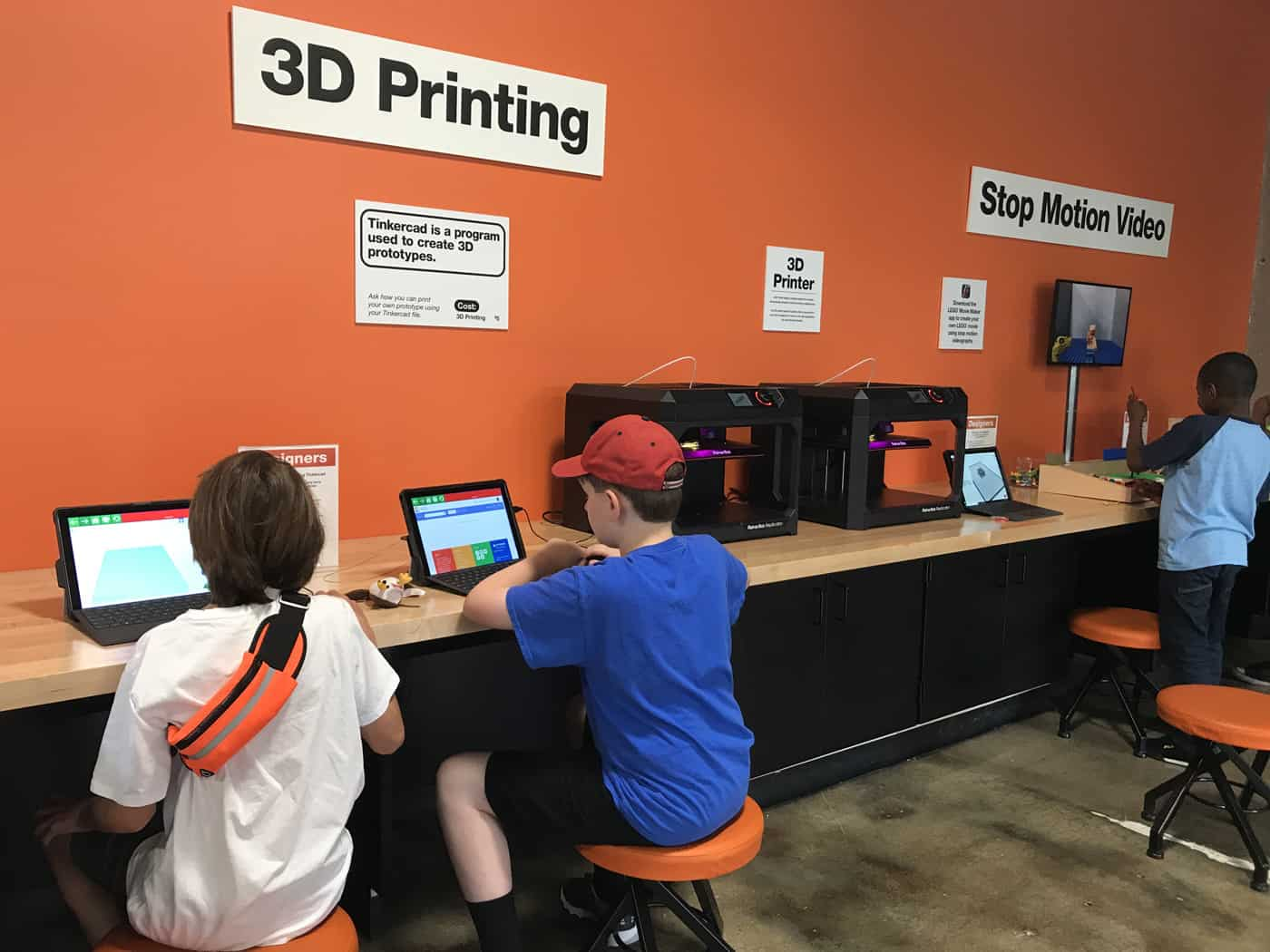 kids working on computers by the 3D printer