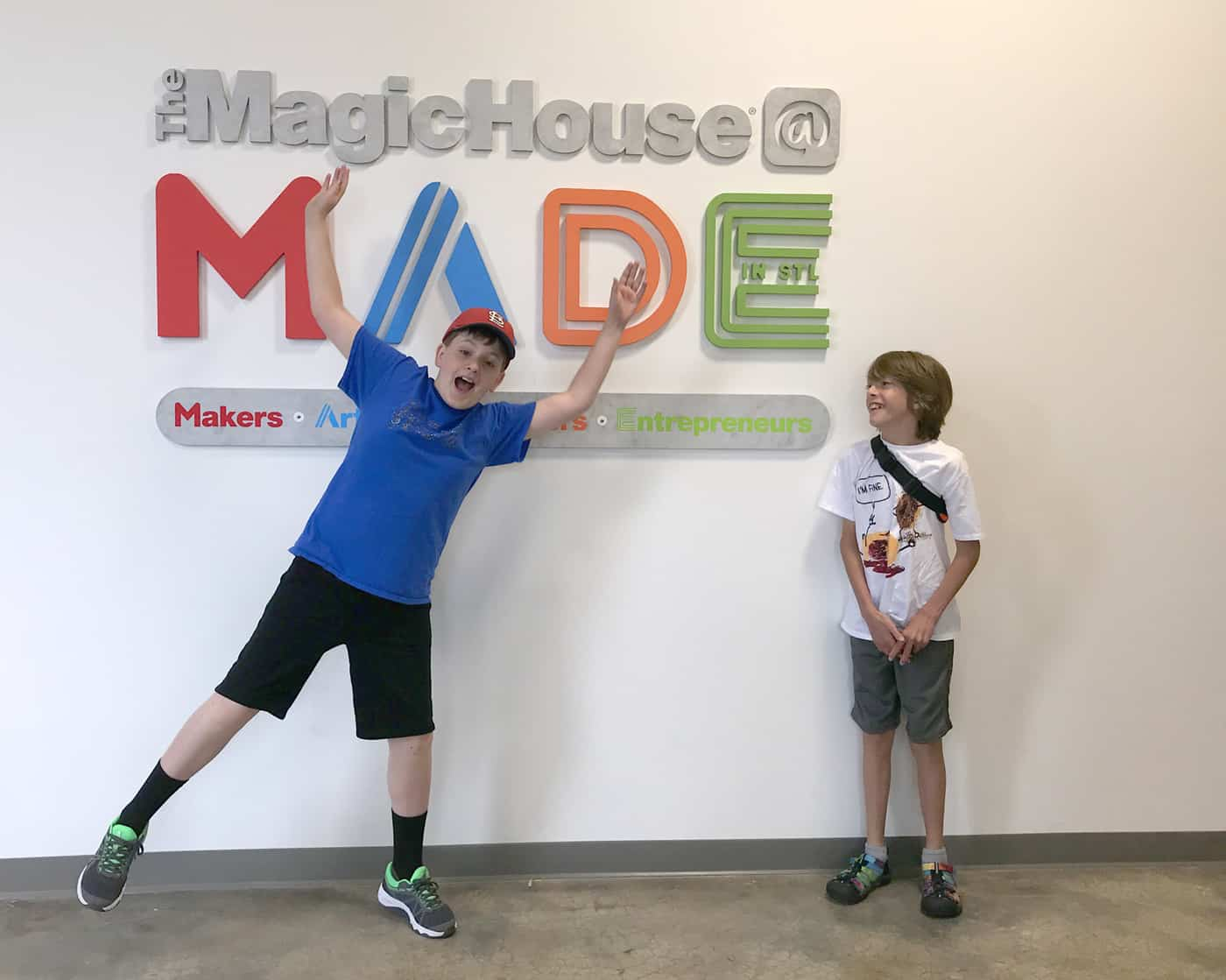 two boys in front of the MADE sign.