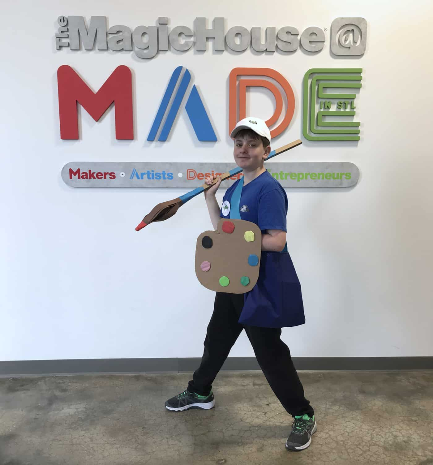 Mitch by the MADE sign, holding a giant cardboard paint brush and paint pallet that he made.