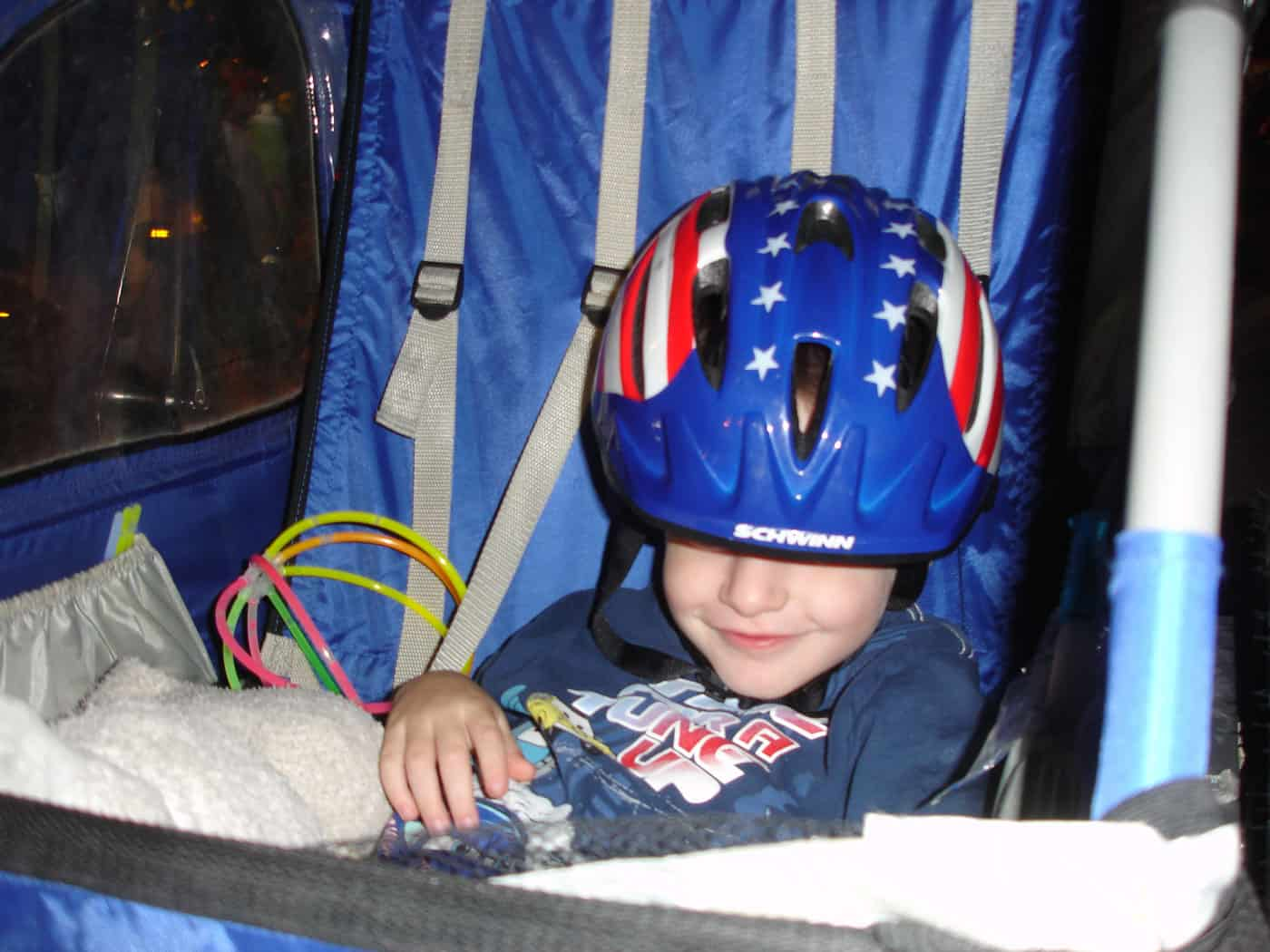 toddler with stars and stripes bike helmet sitting in bike trailer