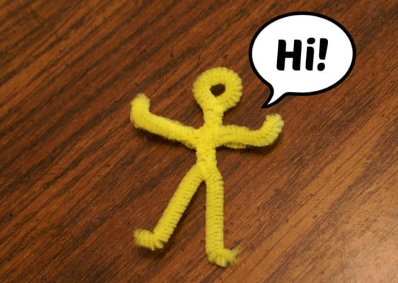 stickman made from yellow fuzzy sticks saying Hi! in a cartoon speech bubble.