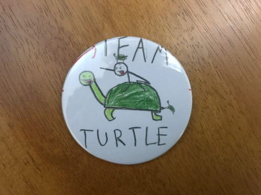 "Button that reads ""Team Turtle"" with child's drawing of a stick man riding a turtle."