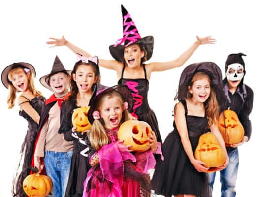 kids in Halloween costumes holding carved pumpkins