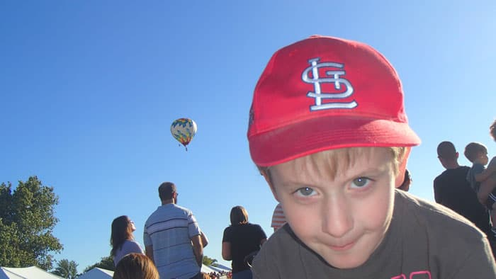 kid in red Cardinals hat smirks at camera with hot air balloons taking off behind him