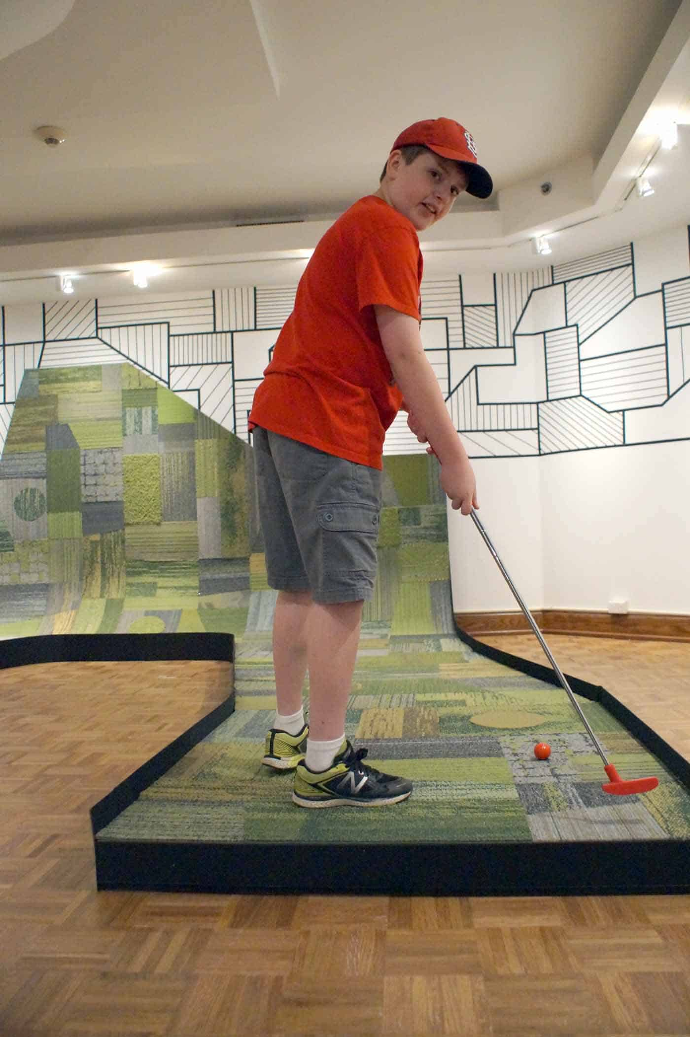 Indoor golf at an art museum. Boy in red shirt plays a mini golf hole made of green carpet squares running up the side of a wall.